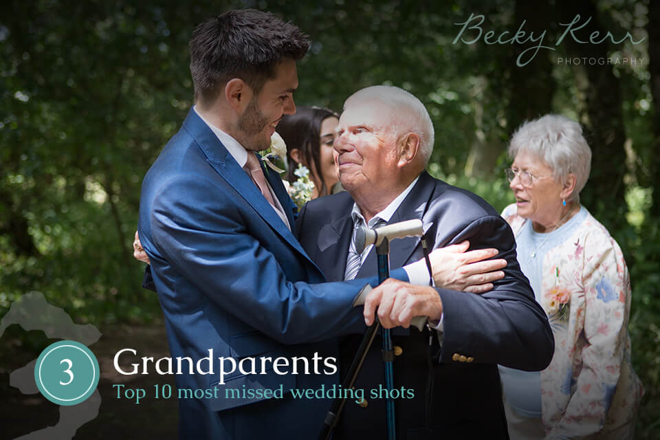 A grandfather and groom embrace at a wedding