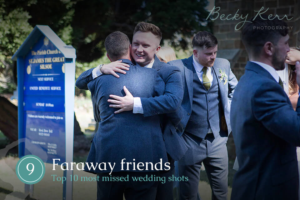 Two friends at a wedding hugging