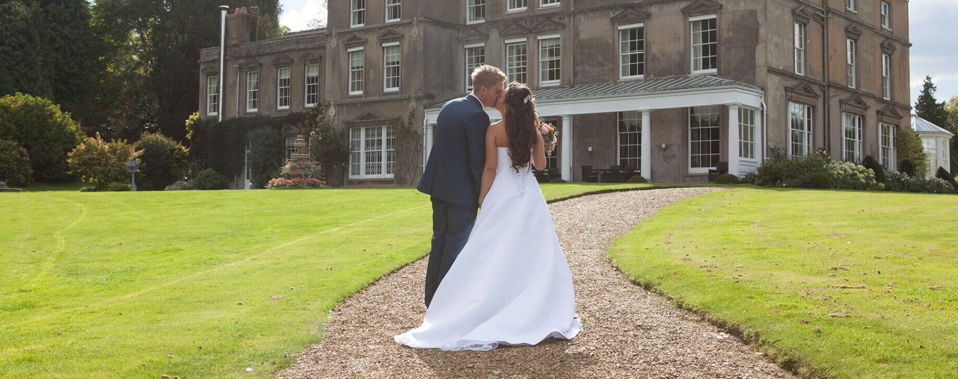 Husband and bride kissing in front of Hexton Manor
