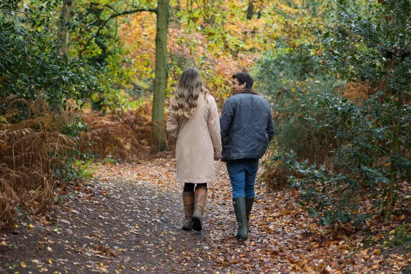 Engaged couple walking through autumn leaves